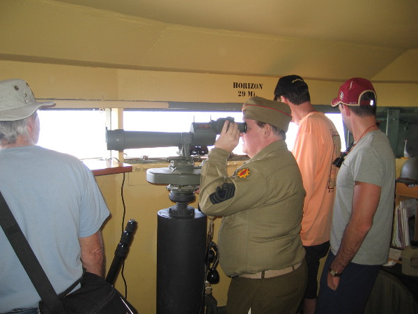A docent in a World War II era uniform demonstrates the use of an azimuth scope, used to scan the ocean for enemy vessels during the war. These spotting scopes gave accurate readings of target positions.
