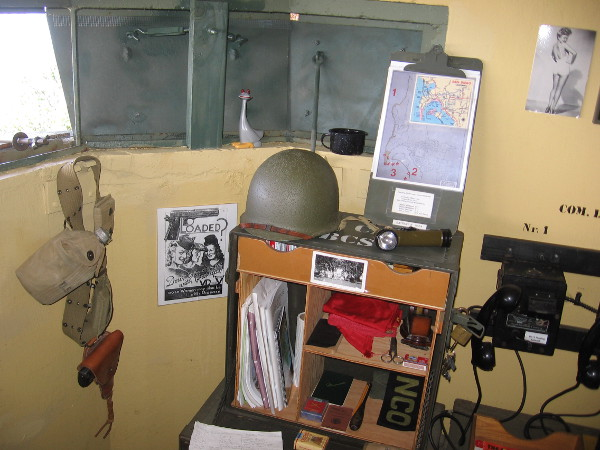 Objects displayed include a map, helmet, canteen and pin-up girl on the wall. A WWII veteran who served at Fort Rosecrans helped to make the bunker's interior appear historically accurate.