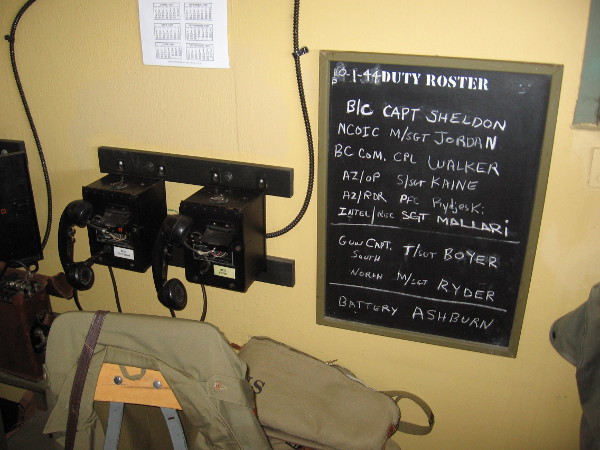 Phones on the wall beside a small Duty Roster chalkboard. The Battery Commander would communicate information to nearby Battery Ashburn.