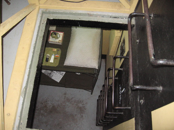 Metal rungs descend into the lower level of the bunker, where visitors can see the small bunkroom and a typical Base End Station.