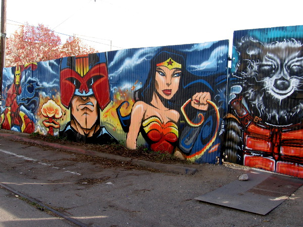 Cool comic book superheroes, villains and other characters are spray painted on a long wall in Logan Heights!