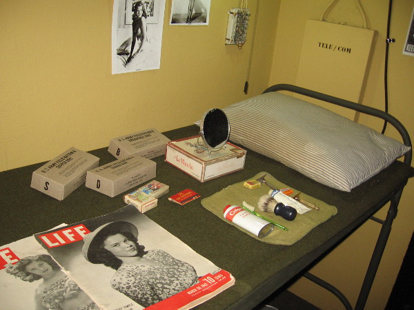 Objects in the bunkroom include toiletries, U. S. Army rations, cigarettes, magazines and pin-ups on the wall.