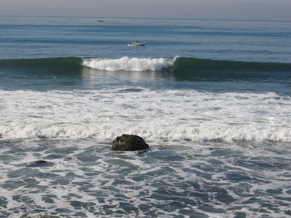 A few rocks stick out of the surf. Fishing boats lie in the water beyond.