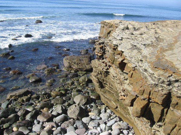 As we head down a short dirt path from the overlook to the tidepool area, we take a closer look at the eroded sandstone cliffs and water-smoothed stones on the narrow beach below.