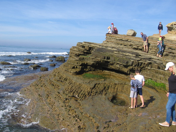 People explore a smooth bowl-like pit in the eroded, layered, uptilted sandstone.