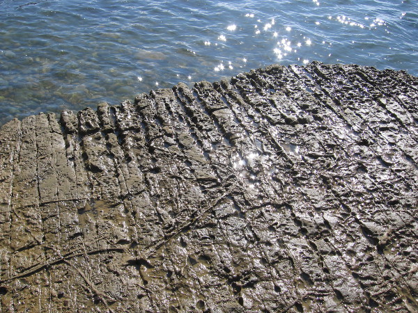 The rock shelf contains parallel fissures and oddly eroded patterns. Over many years the rock is weathered, strangely changes.