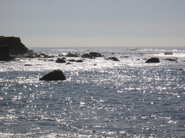 Looking south at light on the water and dark, broken rocks.