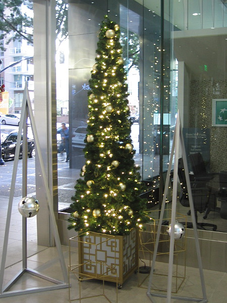 One of the slender Christmas trees adding holiday cheer to the north entrance to the 701 B Street office building.