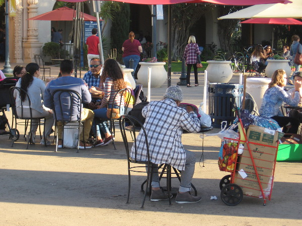 People eat, talk, relax at tables in the Plaza de Panama.