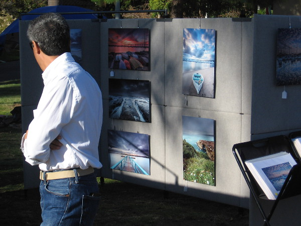 Perusing photographs by a local artist at Art in the Park.