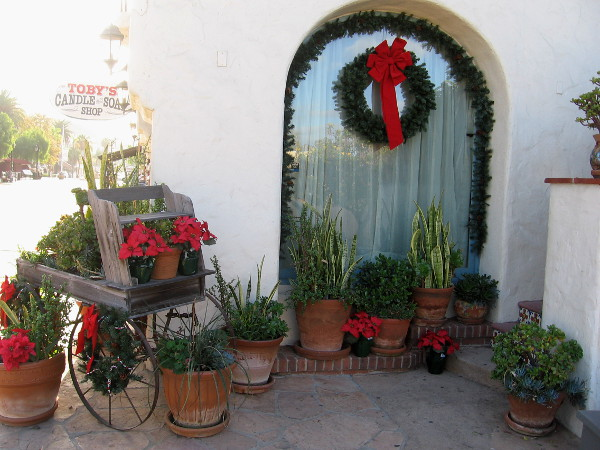 Poinsettias on an old-fashioned cart, and a window wreath decorate one corner of Toby's Candle and Soap Shop.