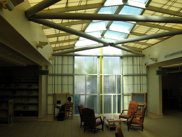 Someone reads near the sail-like cast glass panels of the north window inside the La Jolla Library.