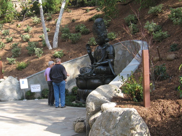 Visitors to the Japanese Friendship Garden gaze at Kannon Bosatsu, a nearly three century old 5750 pound bronze statue recently installed in the Lower Garden by crane!