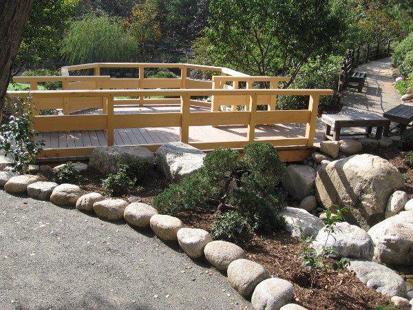 A simple, elegant wooden platform straddles the new stream in the Japanese Friendship Garden.