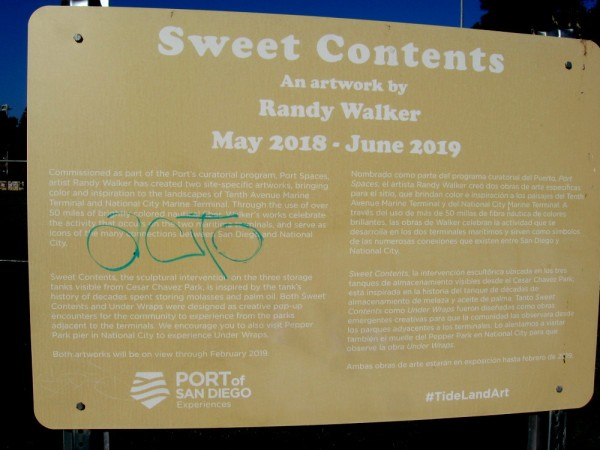 Sign describes Sweet Contents, an artwork by Randy Walker. Differently colored nautical fiber hangs over the exterior of the old molasses and palm oil storage tanks.