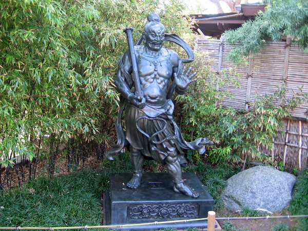 The guardian deity statue that now stands opposite the bonsai collection in the Upper Garden.