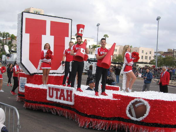 The red and white Utah Utes float with smiling cheer squad passes by.