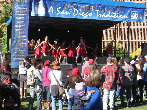 A group of children called Let's Dance for Fun! performs at the small December Nights stage near the Botanical Building.