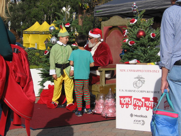 Elsewhere in the rear of the Spreckels Organ Pavilion, Santa confers with an elf before a photo is taken.