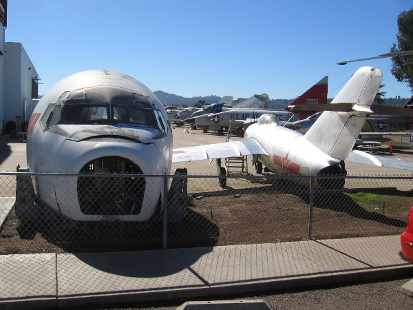 Cockpit exhibits and aircraft in various stages of restoration stand outside the museum annex hangar.
