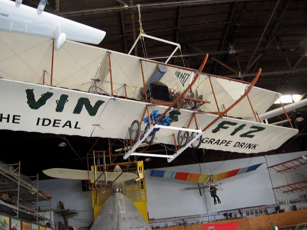 Replica of the Smithsonian's original Vin Fiz Flyer dangles from the ceiling. This one-of-a-kind Wright Brothers airplane was the first aircraft to fly coast-to-coast. The journey took almost three months!