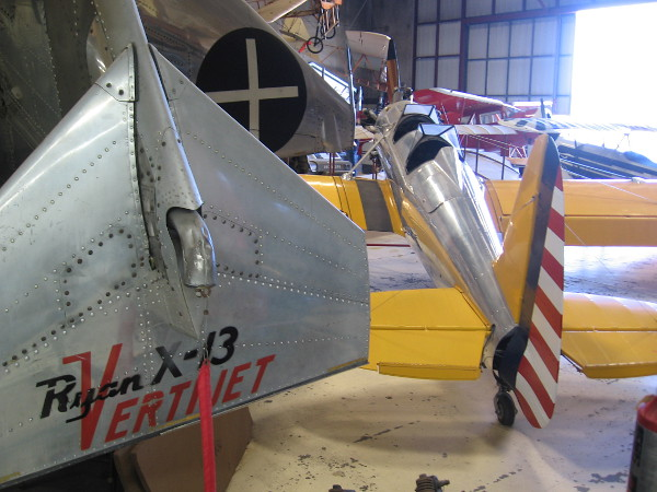 Looking past the Ryan X-13 Vertijet at other exhibits in the annex hangar, including a yellow Ryan Recruit military trainer.