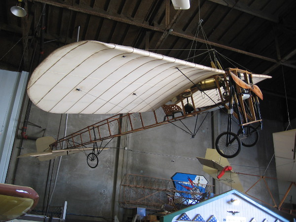 Bleriot XI dangles from the ceiling. The revolutionary 1908 aircraft had a new Anzani engine that could run for one whole hour, allowing it to fly across the English Channel.
