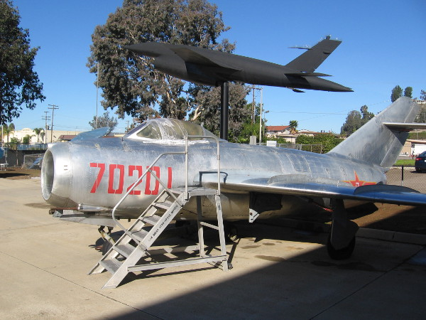 The aircraft in the foreground is a Mikoyan-Gurevich MiG-15. Mounted beyond it is a Ryan Model 147 Lightning Bug jet-powered reconnaissance drone.