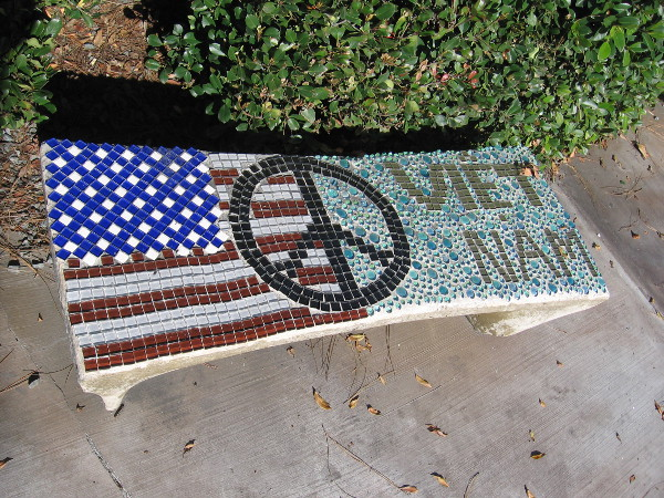 A beautiful tile mosaic bench in the park with American flag and peace sign.