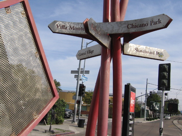 A sign at the trolley station points to various locations of interest, including Villa Montezuma and Chicano Park.