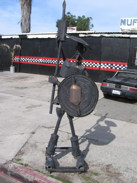 A metal Don Quixote stands guard by a muffler shop.