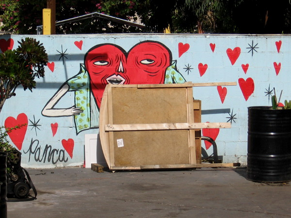 A fun heart in a mural on a neighborhood wall.