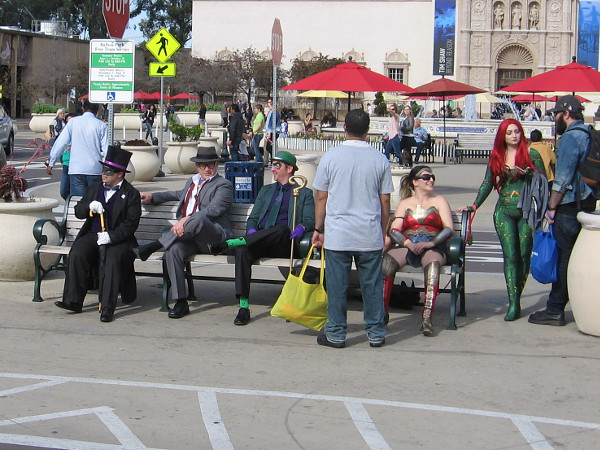 Penguin, Clark Kent, Riddler, Wonder Woman and Mera are tired out and rest on a bench awaiting their trip home.