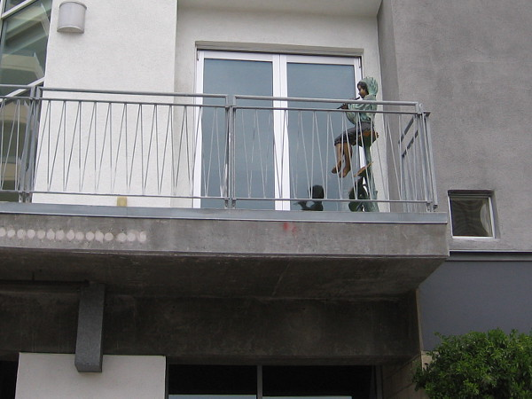 A boy plays a flute up on someone's balcony.