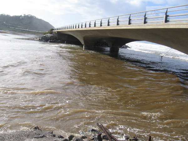 The bridge over the lagoon inlet during a very high tide. The storm-disturbed water appeared very muddy.