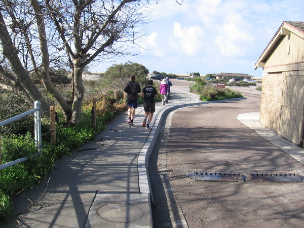 People walk west from Carmel Valley Road into the North Beach Lot of Torrey Pines State Beach.