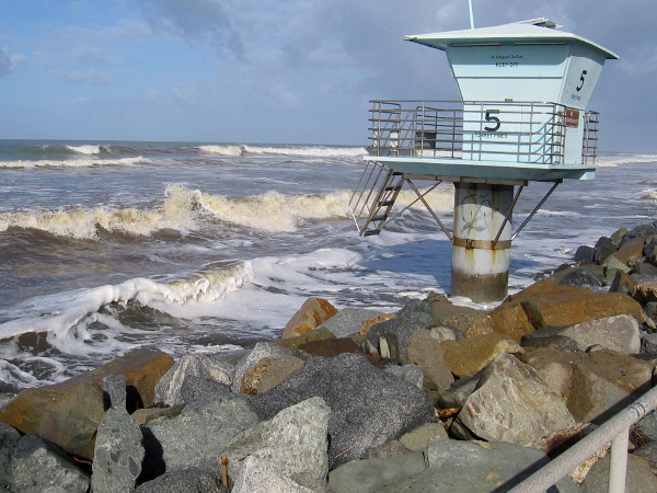 Closed lifeguard Tower 5 at Torrey Pines State Beach is splashed by wild winter waves during high tide.