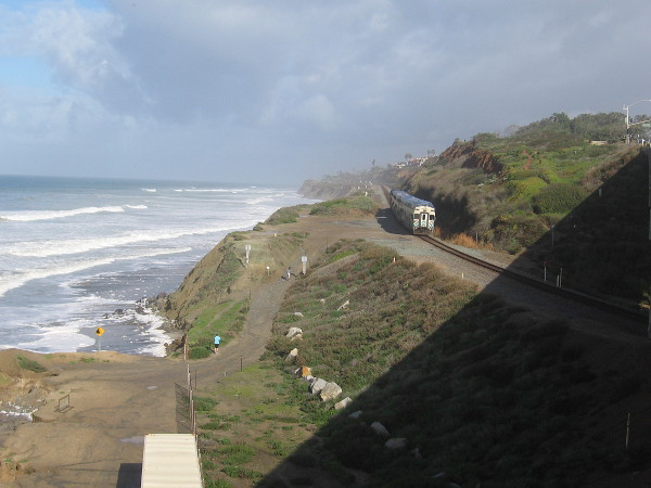 Coaster train moves along tracks north of Torrey Pines State Beach, heading atop scenic sandstone cliffs into Del Mar.
