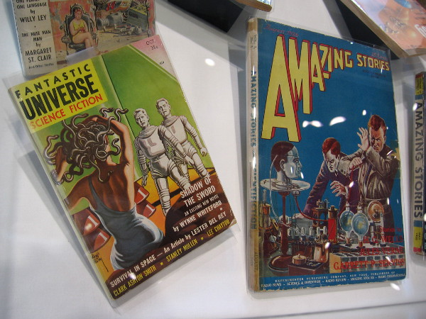 Pulp magazines in a display case recall early visions from science fiction. As human life and technology evolve, the genre also evolves.