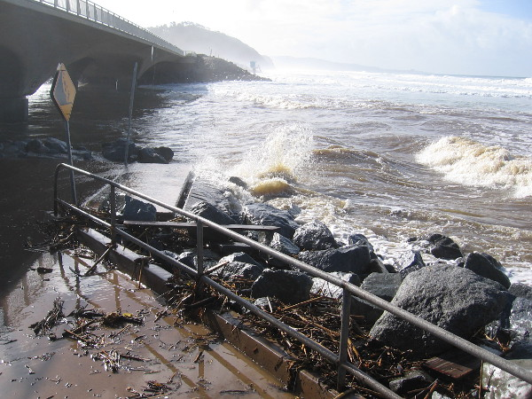 Ocean waves crash toward the North Torrey Pines Road bridge over the entrance to Los Peñasquitos Lagoon.