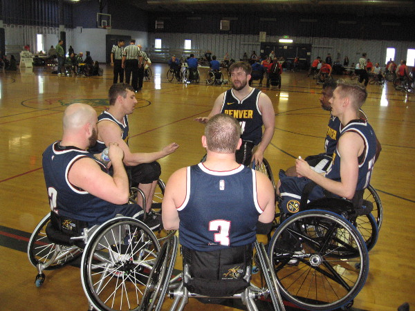 Athletes in the National Wheelchair Basketball Association gather during a time out during the Third Annual Brad Rich Invitational at Balboa Municipal Gymnasium.