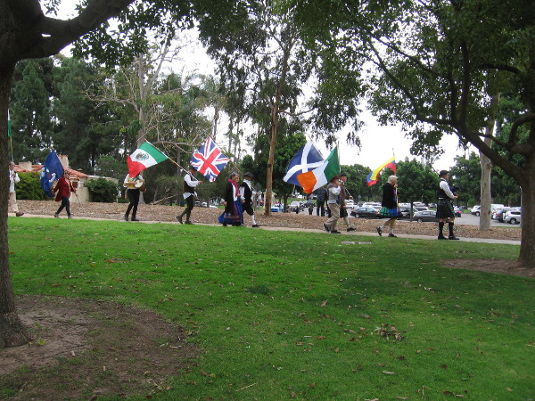 Flags of many nations follow a bagpiper through Balbo Park as the annual International Dance Festival is about to begin.