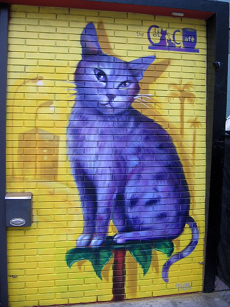 A purple cat on the wall of The Cat Cafe.