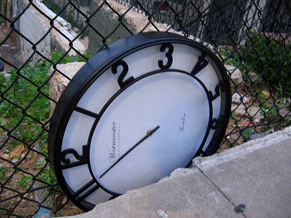 A clock wedged between a sidewalk and fence.