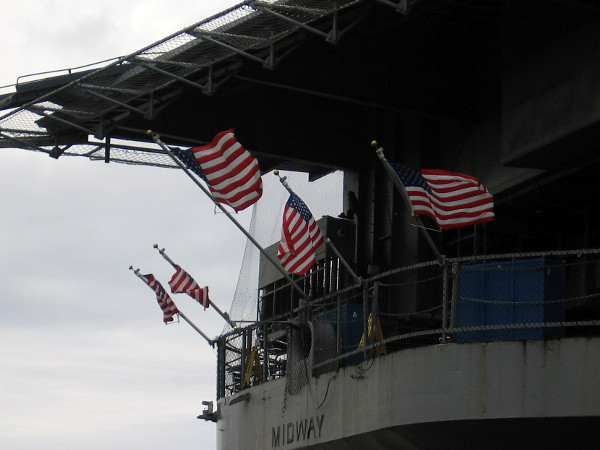Flags whip about in the wind at the stern of the USS Midway on San Diego's Embarcadero.