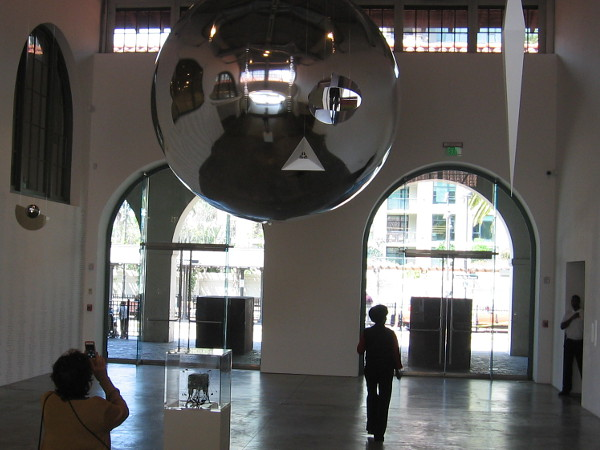A large silvery orb is suspended from the ceiling of the Iris and Matthew Strauss Gallery, inside MCASD's historic Joan and Irwin Jacobs Building.