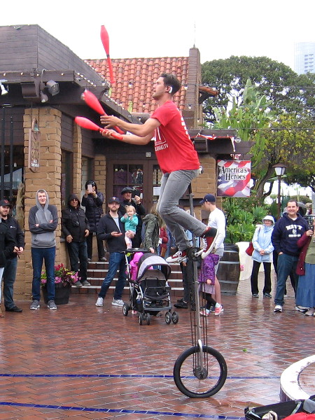 Daniel Israel juggles while high atop a unicycle!
