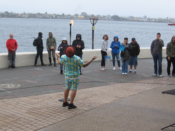 George Gilbert entertains people by the water. For a grand finale, he magically made a pineapple appear under his hat!