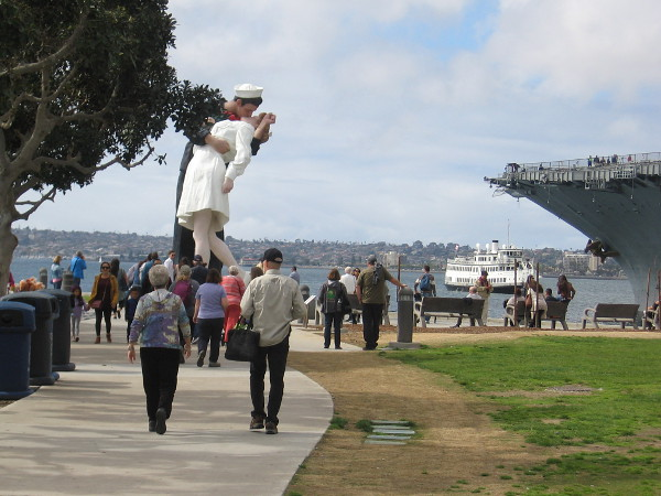 Visitors to San Diego move through the Greatest Generation Walk toward the Embracing Peace statue.