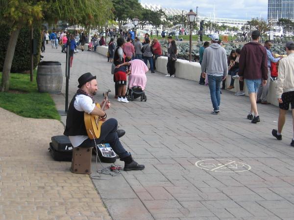 Kyler MacKenzie plays gypsy music on his guitar near Seaport Village.